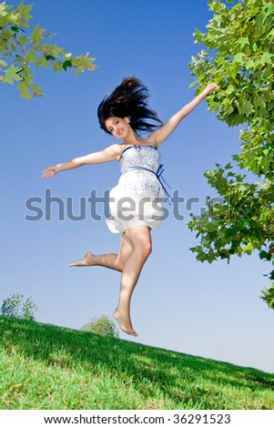 young girl reading happy jumping at the park - stock photo