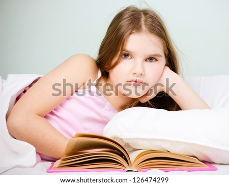young girl reading in bed - stock photo