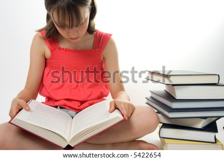 Young girl reading next to a pile of books