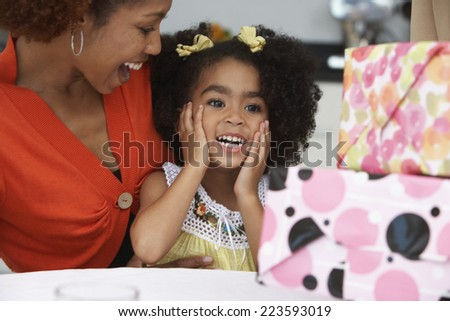 Young girl receiving birthday presents - stock photo