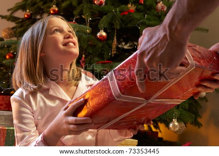 Young Girl Receiving Christmas Present In Front Of Tree - stock photo