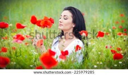 Young girl relaxing in green poppies field. Portrait of beautiful brunette woman posing in a field full of poppies. Beautiful woman enjoying the bright red wild flowers, harmony concept - stock photo