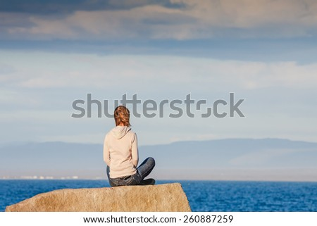 Young girl relaxing near the sea and enjoying her vacation. Calm evening - stock photo