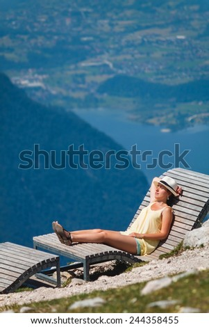 Young girl relaxing on a chaise longue in mountains Dachstein Krippenstein in Austria