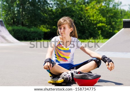 Young girl relaxing with her roller skating gear sitting crossed legged on the asphalt at the park in the summer sunshine - stock photo