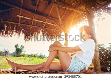 Young girl resting and listening music with headphones in nature under straw roof (intentional sun glare) - stock photo