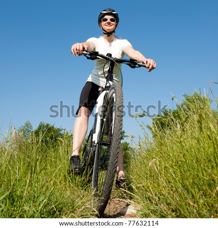Young girl riding a bike on a field path - offroad - stock photo