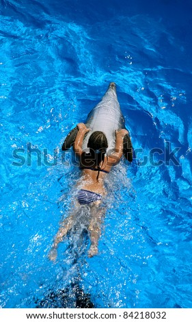 Young girl riding a dolphin - stock photo