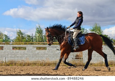 young girl riding a horse - stock photo