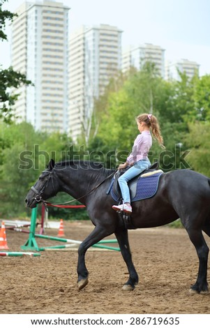 Young girl riding a horse in park near the apartment complex - stock photo