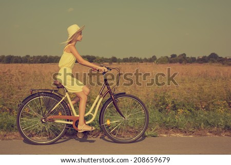 Young girl riding a retro style bike in the countryside. - stock photo