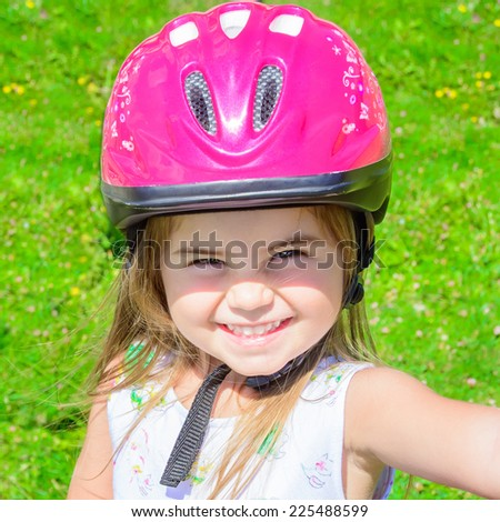 Young girl riding bicycle outdoor smiling with helmet