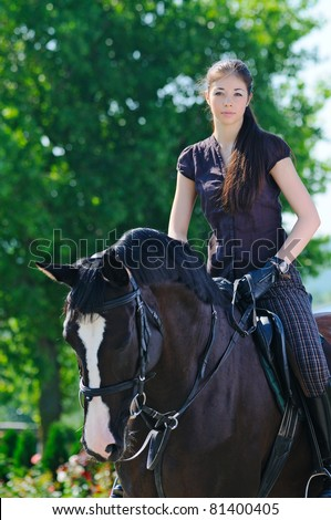 Young  girl riding black sport horse