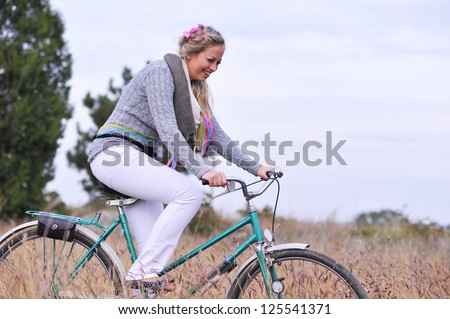 Young girl riding old bicycle outdoors