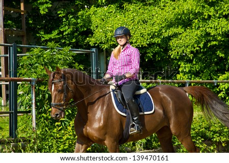 Young girl riding on a brown horse - stock photo