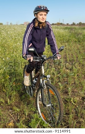Young girl riding on her bicycle on a field - stock photo