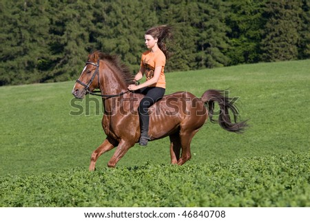 Young girl riding on horse - stock photo