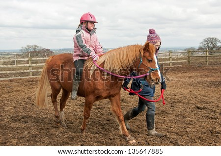 Young girl riding safely on a lead rein, learning her balance without a saddle - stock photo
