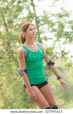 Young girl rollerskating in park - stock photo
