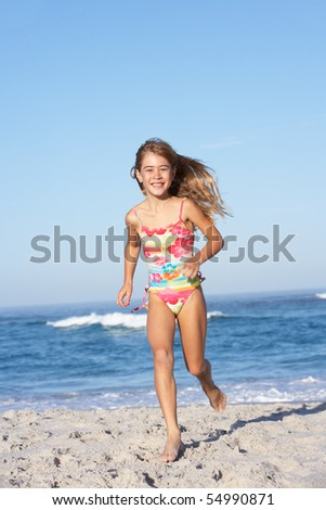 Young Girl Running Along Sandy Beach - stock photo