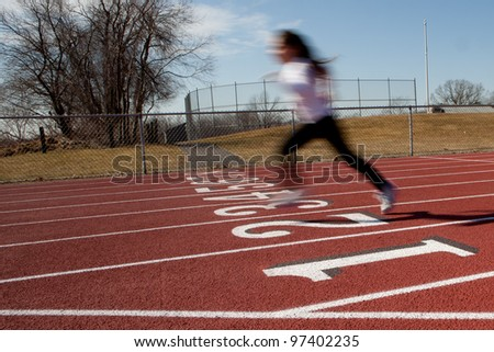 Young girl running on a ruberized track - stock photo