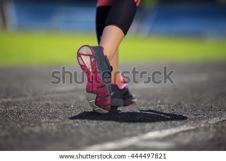 young girl running on the stadium track. Sports shoes