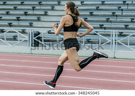 young girl running on track stadium sprint. athletics in summer. beautiful and slim body athletes - stock photo