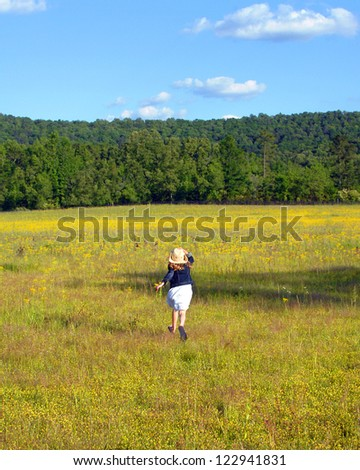 Young girl runs across a field of yellow flowers in rural Alabama.  She is holding her cowboy hat and enjoying nature. - stock photo