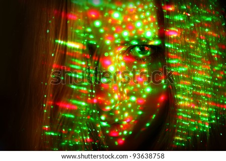 Young girl's face with green and red laser lites - stock photo