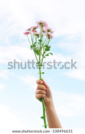 Young girl's hand in the air, holding a bunch of wild flowers against a blue sky. - stock photo