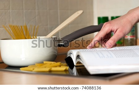 Young girl's hand looking up in a recipes book - stock photo
