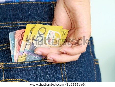 Young girl's hand taking banknote out of jeans pocket - stock photo