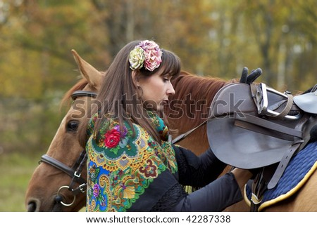 Young girl saddling her horse - stock photo