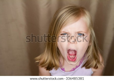 Young girl screams at the camera  - stock photo