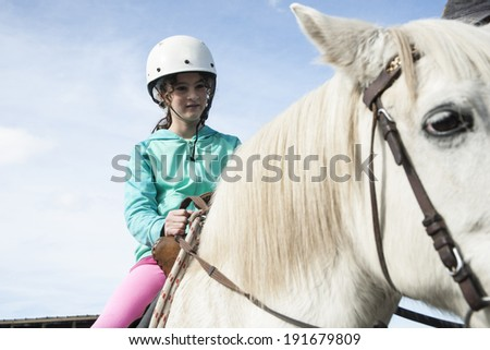 Young girl seated on horseback about to learn to ride on a white horse - stock photo