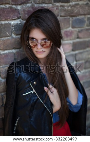 Young girl seductive,solitude ,with long brown hair and a birthmark on face leaning against the brick wall wearing jeans blue shirt and black jacket ,with hand going through hair, wearing sunglasses.  - stock photo