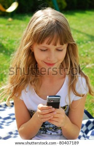 young girl sending SMS by mobile phone sitting outdoor - stock photo