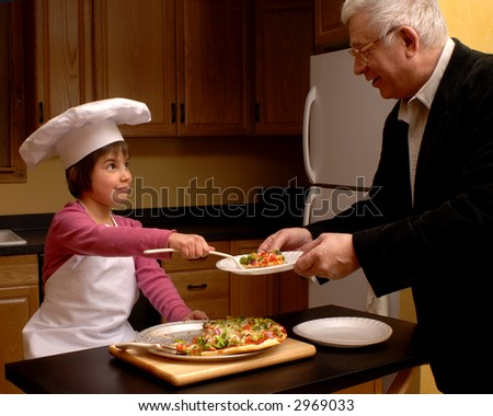 Young girl serving a piece of veggie pizza she'd made to her grandfather. - stock photo