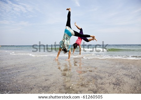 Young girl show an acrobatic on the beach. - stock photo
