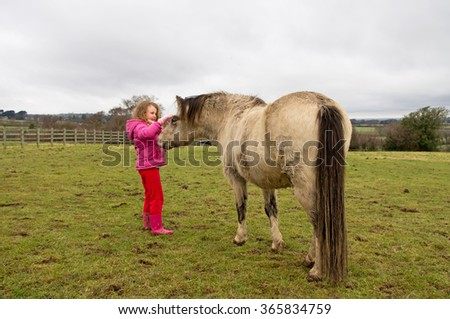 Young girl showing affection towards her pony.