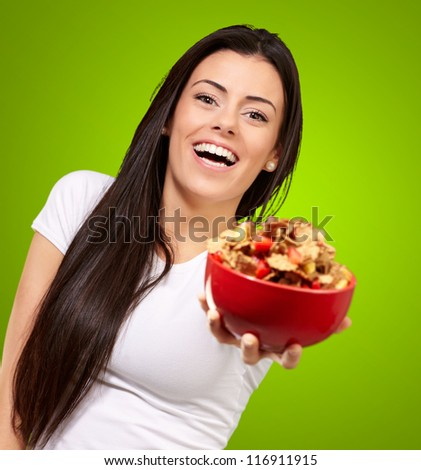 Young Girl Showing Cornflakes Isolated On Green Background
