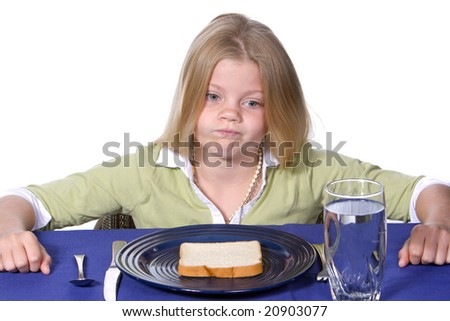 Young girl showing unhappy acceptance of her bread and water dinner. - stock photo
