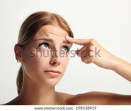 young girl showing with finger her first wrinkle in forehead - stock photo
