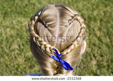 Young girl shows off her hair braided into a heart shape. - stock photo