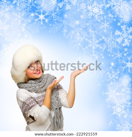 Young girl shows welcome gesture on blue winter background - stock photo