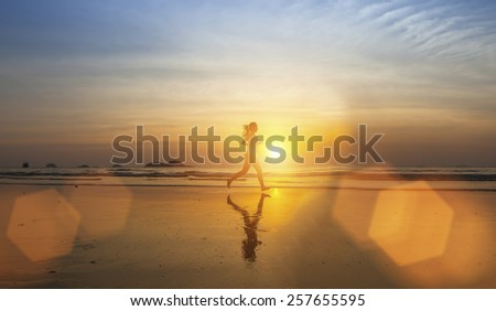 Young girl silhouette Jogging on sea beach in rays of the sunset.  - stock photo