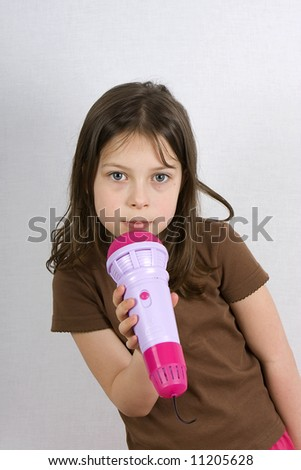 Young Girl singing into a Toy Microphone - stock photo