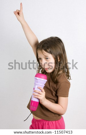 Young Girl Singing into her Toy Microphone with her Hand in the Air - stock photo