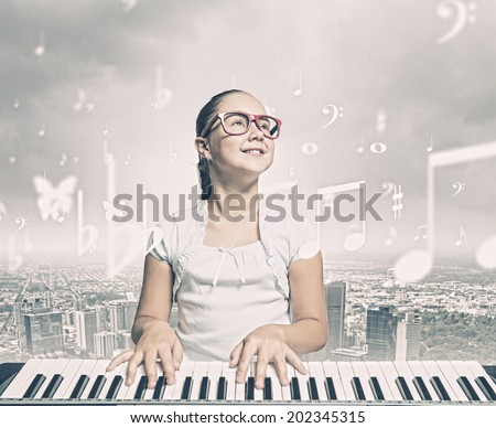 Young girl sitiing at digital piano with red glasses - stock photo