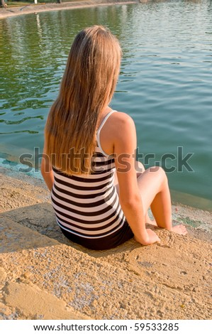 Young girl siting nearby the lake - stock photo